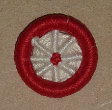 'Blandford Cartwheel' type of Dorset button, made in red and white yarn
