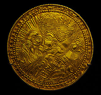 Germanic religion (aboriginal) -  A Migration Period Germanic gold bracteate featuring a depiction of a bird, horse, and stylized head wearing a Suebian knot sometimes theorized to represent Germanic god Wōden and what would later become Sleipnir and Hugin or Munin in Germanic mythology, later attested in the form of Norse mythology. The runic inscription includes the religious term alu.