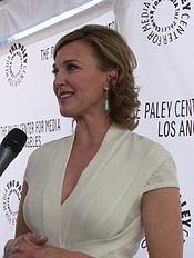 "A blond woman shown smiling as she is being interviewed with a microphone pointed towards her. She is wearing a white dress with turquoise earrings, and is standing behind a backdrop with the words ""THE PALEY CENTER FOR MEDIA"" followed by the words ""LOS ANGELES""."