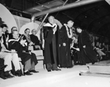 DeMille standing at a graduation ceremony in graduation robes among others sitting and applauding