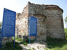 Southeast view of a church. Two of the three apses are visible, the middle one larger than the side ones. Blue signs with information in Bulgarian and English next to the building.