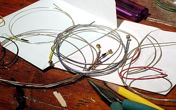 violin strings, used and new, coiled on a work...