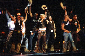 "Music (Madonna album) - Madonna and her dancers dressed as cowboys during the performance of ""Don't Tell Me"" on the Drowned World Tour, 2001"