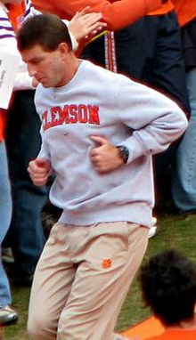 Coach Swinney in a grey sweatshirt and khaki pants, while running, with persons at rear.