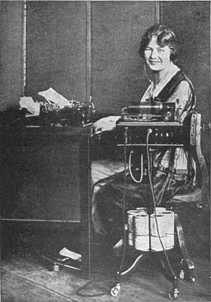 Dictation machine - Transcribing dictation with a Dictaphone wax cylinder dictation machine, in the early 1920s.  Note supply of extra wax cylinders on lower part of stand.