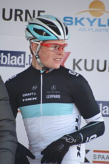 A man in his mid-twenties wearing a cycling jersey with black sleeves, a white torso, and a blue stripe separating them, along with red-framed glasses. He is looking to his left off-frame.