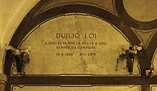 A marble gravestone on the wall of a crypt