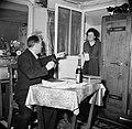 Echtpaar in de woonkamer de man zittend aan tafel terwijl de vrouw binnenkomt m, Bestanddeelnr 252-9336.jpg