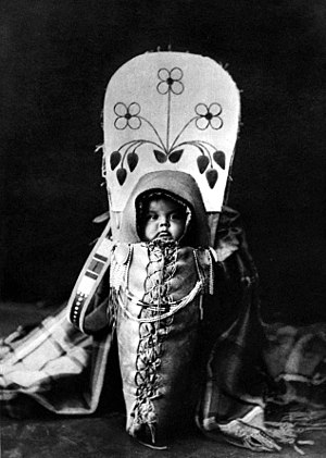 Papoose - A child carrier, especially ones resembling those of Native Americans, is sometimes referred to as a Papoose.