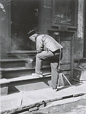 Black and white photo of a Chinese man, who has a very long queue falling along his back, bending over a steaming pan on a step.