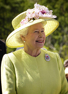 Elderly lady with a yellow hat and grey hair is smiling in outdoor setting.