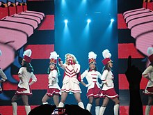Picture of several women wearing white and red majorette uniforms. The one in the middle is blonde and is holding a baton in front of her. The backdrops show a red and white animation
