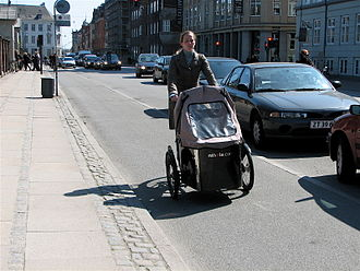 Cycling in Copenhagen - Typical design of bicycle facilities in Copenhagen.  The cycle track runs next to the sidewalk and is separated from motor vehicle traffic by a curb and parked cars