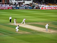 Men in cricket whites play upon the green grass cricket field amidst the stadium.