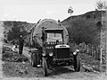 Front on view of a Leyland truck transporting a piece of Kauri along a dirt road (AM 75773-1).jpg