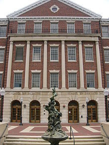 "Front facade of a brick building with columns that has inscriptions above the entrance that read ""School of Medicine"" on the left and ""School of Dentistry"" on the right. In the foreground is a bronze statue."