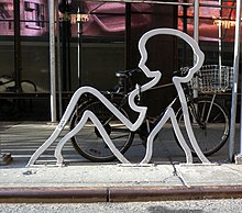The outline of a silhouette of a naked woman leaning back, in galvanized steel, on a street curb. It has a bicycle with a shopping basket chained to it.