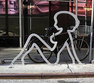 Очертание силуэта откинувшейся обнаженной женщины из оцинкованной стали на уличном бордюре. К нему прикован велосипед с корзиной для покупок.