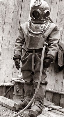 Standing figure of a diver clad in copper helmet, heavy canvas diving suit, with gloves, chest weight and weighted boots