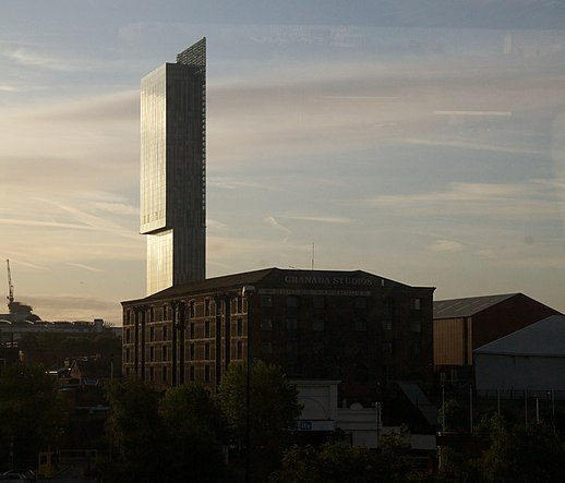 Reflective glazing and natural light is used to accentuate the tower's crystalline form throughout the course of the day. Granada Studios Building and Beetham Tower in Manchester.jpg