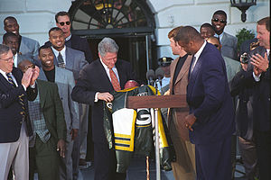 Brett Favre - Favre (in a brown suit) with teammate Reggie White presenting President Bill Clinton with a Packers jacket in a May 1997 ceremony following the Packers' Super Bowl victory that year