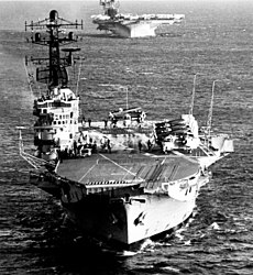 An aerial photo of an aircraft carrier with several aircraft on her flight deck. Another carrier is visible in the background.