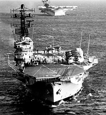 "The retirement of the aircraft carrier HMAS Melbourne without replacement in 1982 marked a shift away from the policy of ""forward defence"". HMAS Melbourne (R21) and USS Midway (CV-41) underway, 16 May 1981 (6380752).jpg"