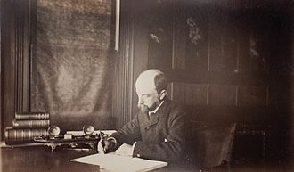 Henry Adams - Henry Adams seated at desk in dark coat, writing, 1883