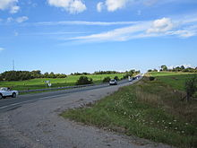 A two-lane undivided road passing through rolling farmland and woodland