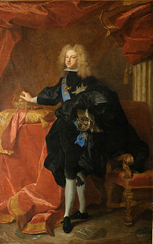 Standing man with light, curly hair, dressed in dark-colored royal finery