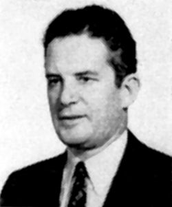 Grainy older portrait of a caucasian man wearing a suit and a tie. He is facing left, and has dark curly hair.