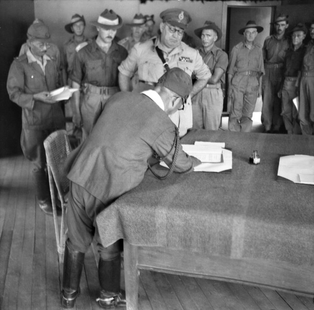Masao Baba, Lieutenant General of the Japanese 37th Army signs the surrender document in Labuan, British Borneo, being watched by Australian Major General George Wootten and other Australian units.