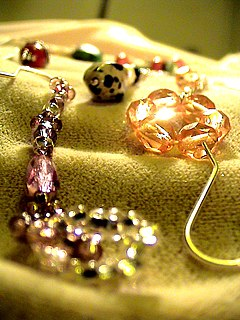 piece of jewellery incorporated into clothing, or worn by itself on the body (typically on a necklace)