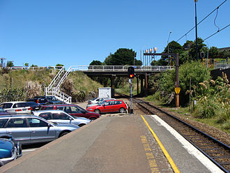 """Johnsonville railway station - The (old) Broderick Road overbridge crosses the line just south of the station. This photo showing commuter """"park and ride"""" parking was taken before the platform was lengthened in 2010"""