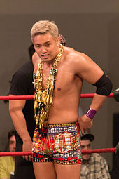 Kazuchika Okada, a Japanese man with blonde hair, wearing a golden garland as well as red and gold trunks while standing in a professional wrestling ring