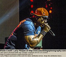 On a brightly-lit stage, an African-American man wearing an orange baseball cap, glasses and a blue shirt raps into a microphone.
