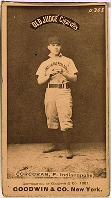 "Baseball card with photo of full shot of man standing wearing a baseball uniform.  The cap is dark and the shirt says ""Indianapolis"".  Near the top of the photo are the words ""Old Judge Cigarettes"" and near the bottom are the words :CORCORAN, P, Indianapolis.  At the bottom of the card beneath the photo it states ""GOODWIN & CO. New York."