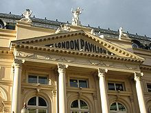 "Colour photograph of a neoclassical building with a number of statues on the roof and a decorative façade consisting of four columns topped by a triangular pediment. Letters spelling ""London Pavilion"" are contained within the tympanum."