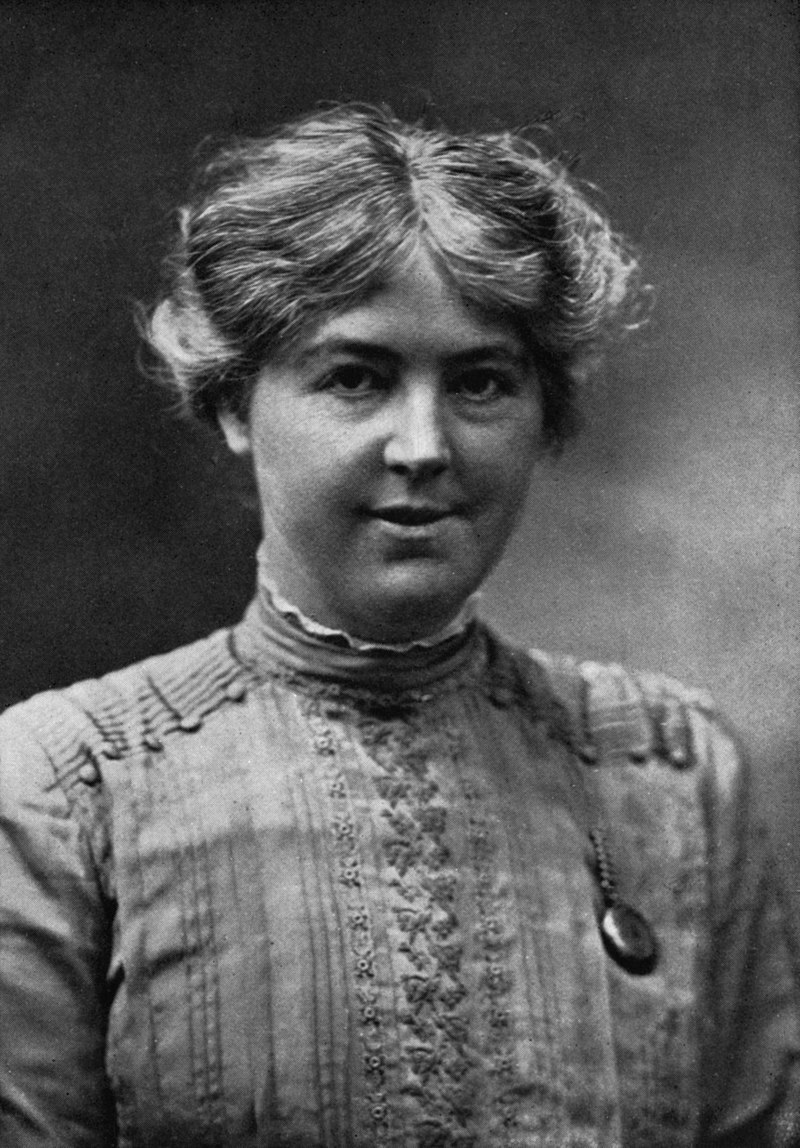 Monochrome photograph portrait of a woman in her twenties, shown from the bust upward, the woman wearing a vertical-patterned blouse decorated by a row of buttons between the shoulders and the closed collar, her face directly forward gazing at the viewer, her cheeks prominent and fleshy, the mouth slightly opened in a tight smile, the coarse, sun-bleached sandy-coloured hair parted in the middle, extending to the ears in an overall loose wave with flyaway strands