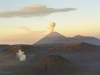 A brown volcano in the center with white smoke emanating from its peak, a cloudy sky fading from blue at the top through yellow in the middle to red at the horizon, and brown mountains in the foreground.