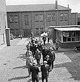 Mannen lopend op fabrieksterrein met een portiersloge, op de achtergrond een ijs, Bestanddeelnr 255-8540.jpg