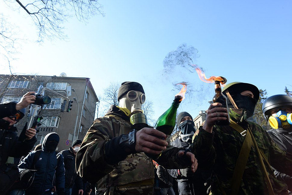 Masked and hooded protesters holding Molotov Cocktails seen during clashes in Ukraine, Kyiv. Events of February 18, 2014