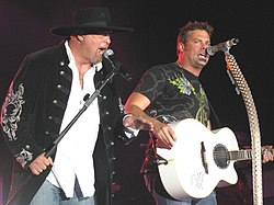 Eddie Montgomery and Troy Gentry of Montgomery Gentry singing into microphones, with Gentry also playing a white guitar