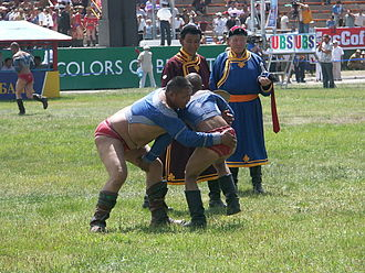 "Mongolian wrestling - A common Mongolian wrestling match with ""zasuul"" of each wrestler looking on"