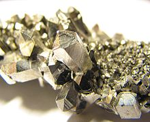A lump of gray shining crystals with hexagonal facetting