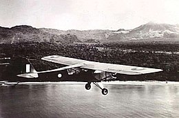 Single-engined high-wing light plane flying over water, with jungle terrain in background