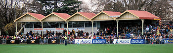 A grassed sporting oval with an old stand with a yellow and red roof, filled with spectators
