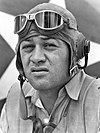 Head of a squinting man wearing a shirt unbottoned at the collar and a cloth aviator's cap with headphones built into the ear flaps, an unbuckled chin strap, and goggles pushed up onto his forehead.