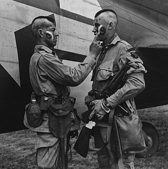 101st Airborne Division - Private Ware applies last second war paint to Private Plaudo in England June 1944.
