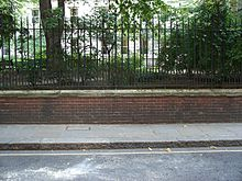A brick wall topped by metal railings stands at the side of a tarmac road. Behind the wall, grass and trees are visible, growing at the height of the top of the wall.
